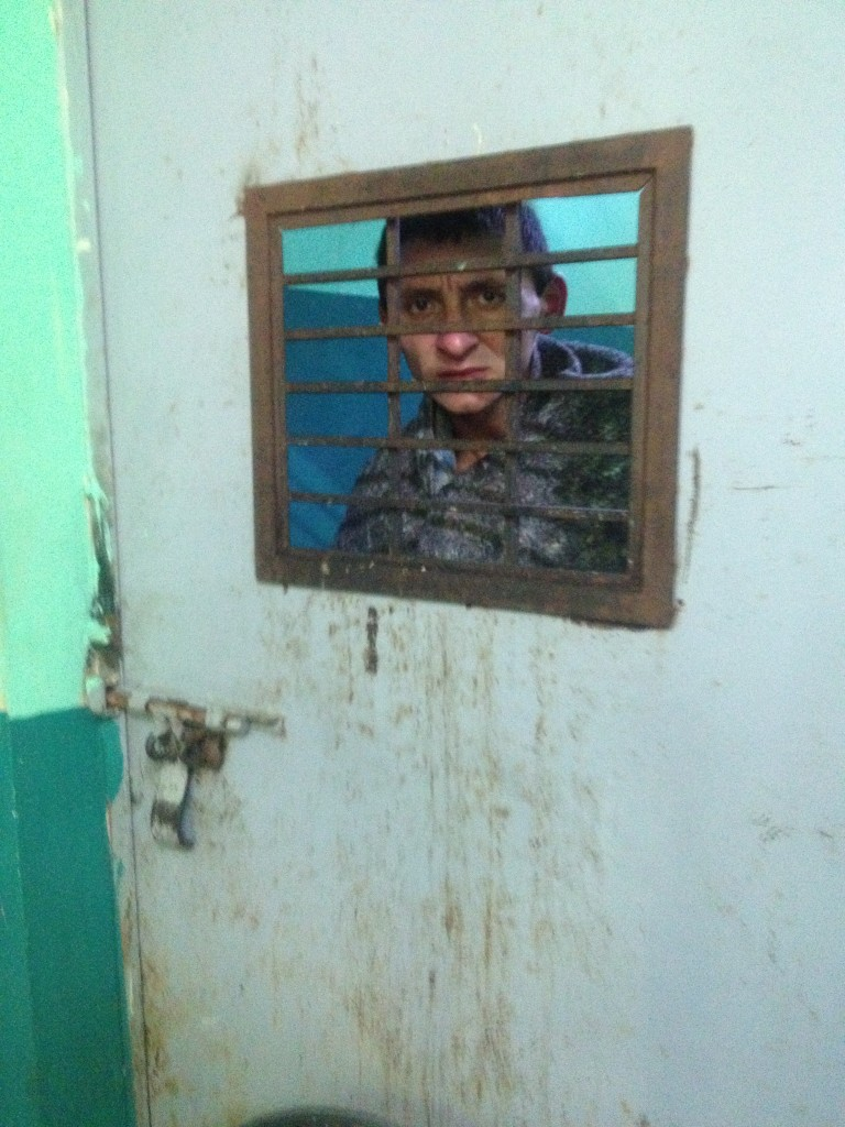 Person in isolation cell in Guatemala psychiatric hospital
